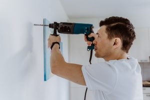 Husband for hour home repairing service. Portrait of handyman drilling a hole in wall